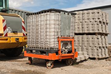 Ein Wassertank für Bauwasser steht auf einem Plattenwagen