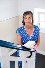 woman cleaning banisters