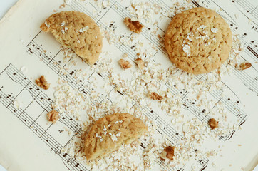Homemade oatmeal cookies with walnut on vintage music sheet
