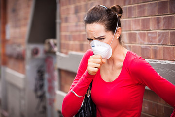 Woman wearing facemask coughing