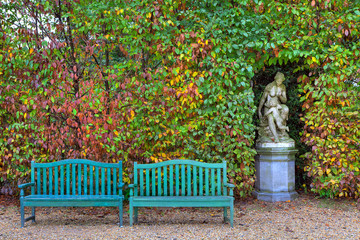 Benches and sculpture in autumnal park,