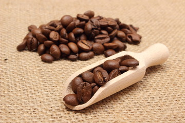 Coffee beans on wooden spoon and heap of coffee