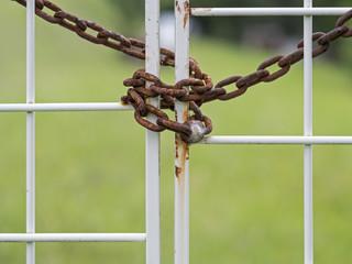 Rusty chain locks a white gate