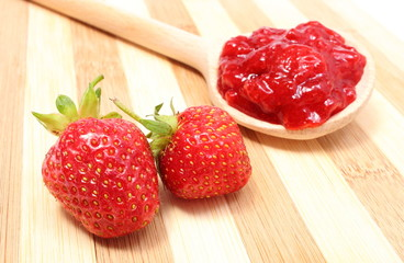 Strawberry jam on wooden spoon with fresh fruits