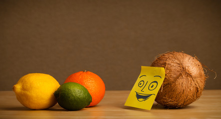 Coconut with post-it note smiling at citrus fruits