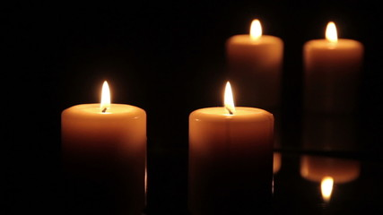 Two candles burning in front of a mirror
