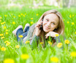 girl lying on grass with dandelions and talking on the phone