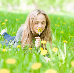 beautiful girl lying on the grass and smelling dandelion