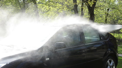 Closeup of car wash clean on sunlight with pressured water jet
