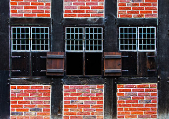 Windows with shutters in brick wall of the half timbered house