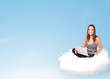 Young woman with laptop sitting on cloud with copy space
