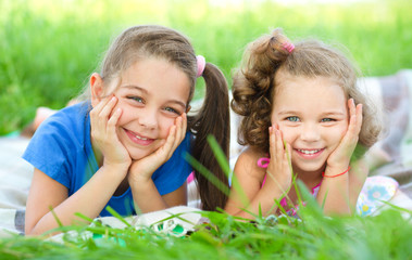 Two little girls are laying on green grass
