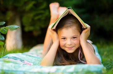 Little girl is hiding under book outdoors