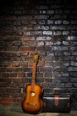 guitar and retro bag on brick wall background