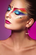 Vertical portrait of cute adult girl with multicolor make up on