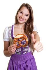 Frau im lila Dirndl mit Brezel zeigt den Daumen hoch