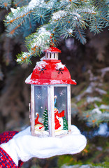 Beautiful red decorative Christmas lantern on warm mittens