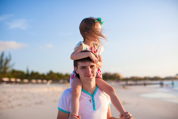 Little cute girl riding on her dad walking by the beach