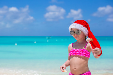 Little cute girl in red Santa hat on tropical beach