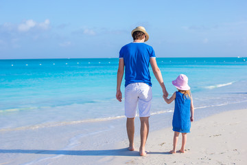 Adorable little girl and father at beach during summer vacation