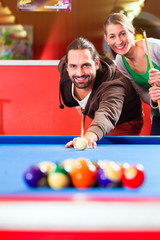 Couple playing pool billiard game