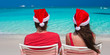 Happy romantic couple in red Santa Hats at tropical beach
