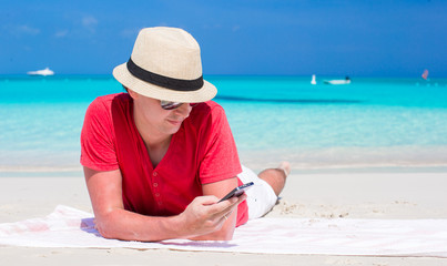 Young man with cell phone on tropical white beach