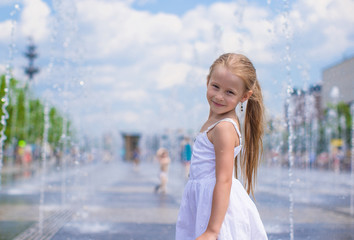 Little cute girl have fun in open street fountain at hot summer