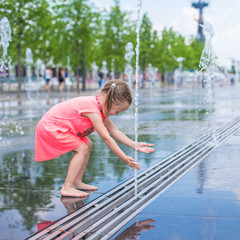 Little girl have fun in open street fountain at hot summer day
