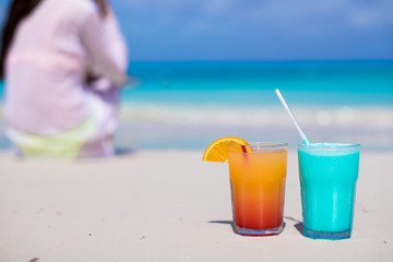 Close up tasty cocktails on beach background young woman