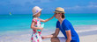 Little girl rubs sunscreen on nose of her dad