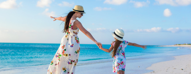 Beautiful mother and her adorable little daughter enjoy summer