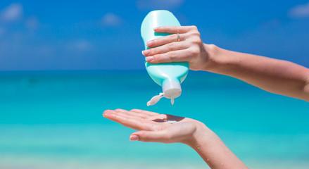 Woman hands putting sunscreen from suncream bottle