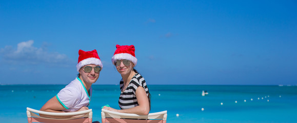 Young couple in Santa hats during beach vacation