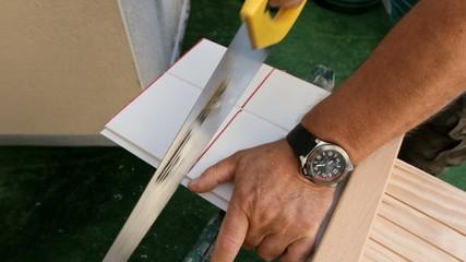 Man sawing board at home