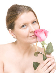 attractive mid adult woman with a pink rose, female face of beau