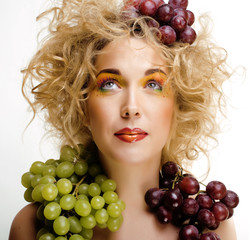 cute blond woman with creative make up and grapes