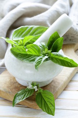 fresh green basil leaves in a marble mortar