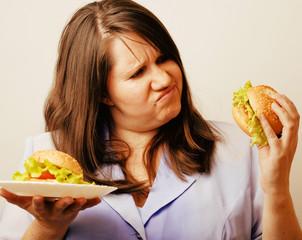 fat white woman having choice between hamburger and salad