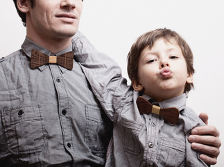 father with son in bowties on white background, casual look