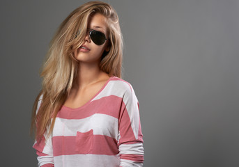 beautiful girl in sunglasses on gray background
