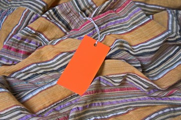 orange tag with empty space for your writing on a striped cloth
