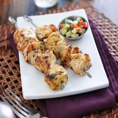 two grilled chicken sishkabobs with cucumber salad