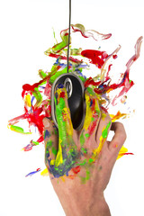 Hand holding a computer mouse with paint all around