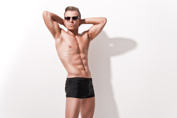 Male muscled underwear model wearing black shorts and vintage su