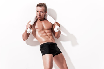 Male muscled underwear model wearing black shorts. Holding white