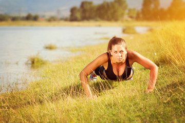 Fit young woman doing pushups outdoors on sunny summer day