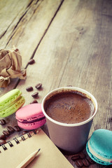macaroons, espresso coffee cup and sketch book on wooden rustic