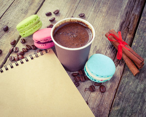 macaroons, espresso coffee cup, cinnamon sticks and sketch book