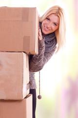 Frau lächelt hinter Umzugskartons hervor